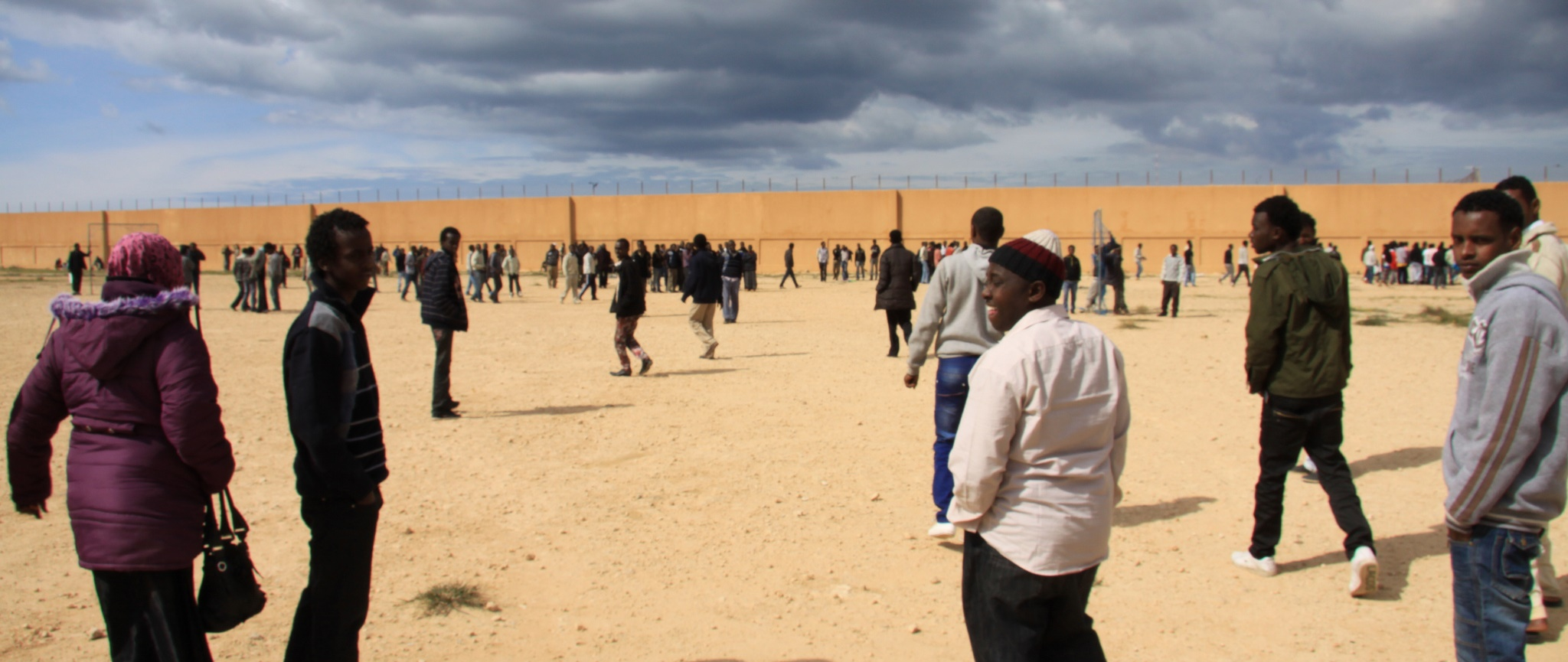 People from sub-Saharan Africa, including Somalis and Eritreans, talk in the vast yard of the detention center of Benghazi (UNHCR)